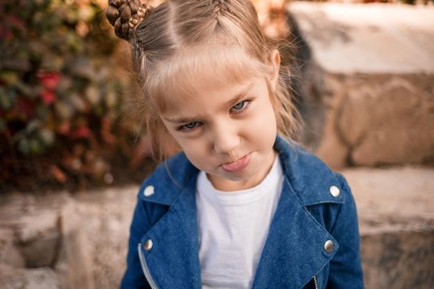 Uma linda garota de cerca de sete anos em uma jaqueta jeans olha para a câmera e faz caretas