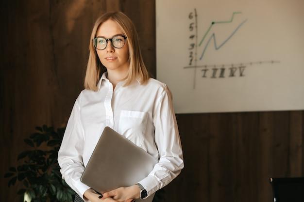 Uma linda garota de negócios em uma camisa branca e óculos está com um laptop nas mãos no escritório contra um quadro-negro com um gráfico do crescimento da empresa