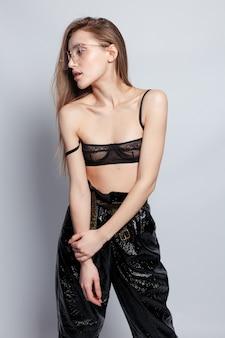 Uma linda garota de óculos com uma armação de metal está de pé na janela. look da moda preto. olhe para a camera.