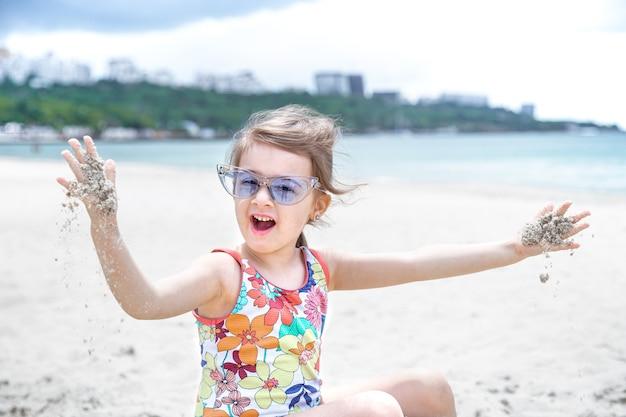 Uma linda garota de óculos está brincando na areia na praia à beira-mar. entretenimento e recreação de verão.