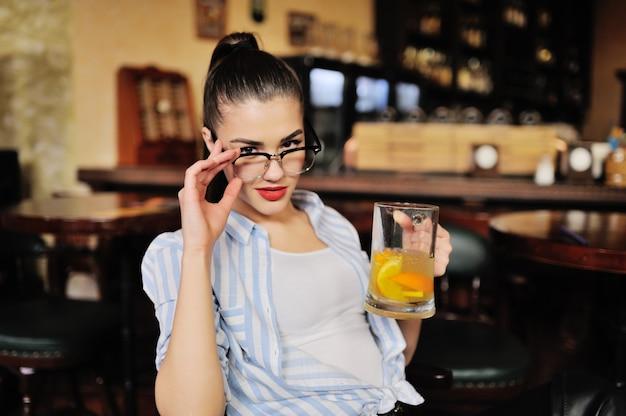 Uma linda garota de óculos está segurando uma caneca com cerveja ou um coquetel de laranja na frente de um bar ou pub