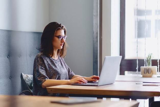 Uma linda garota de óculos trabalha para um laptop em um café