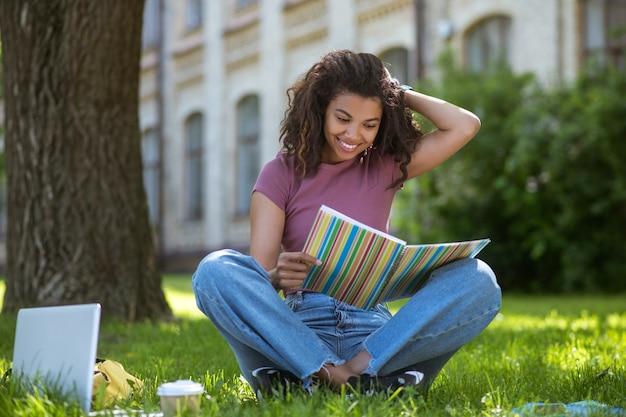 Uma linda garota de pele escura estudando no parque