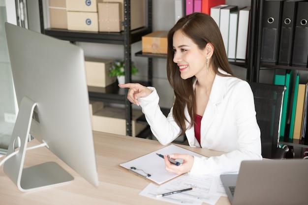 Uma linda garota de terno branco está fazendo seu negócio usando a internet e o computador.