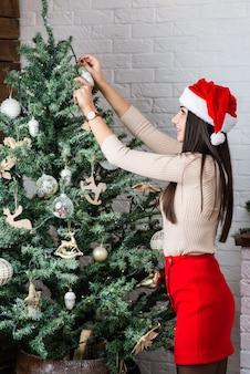 Uma linda garota decora uma árvore de natal.