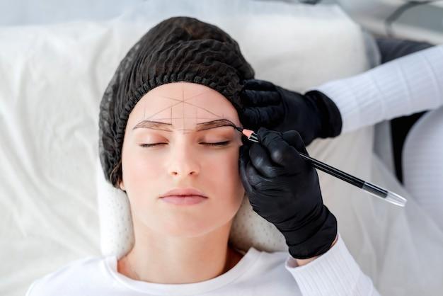 Uma linda garota deita enquanto o mestre da maquiagem permanente desenha as sobrancelhas com um lápis