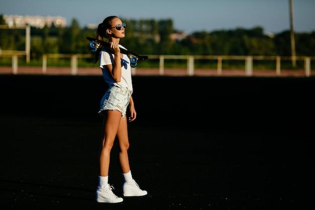 Uma linda garota detém um skate no ombro na sunset.
