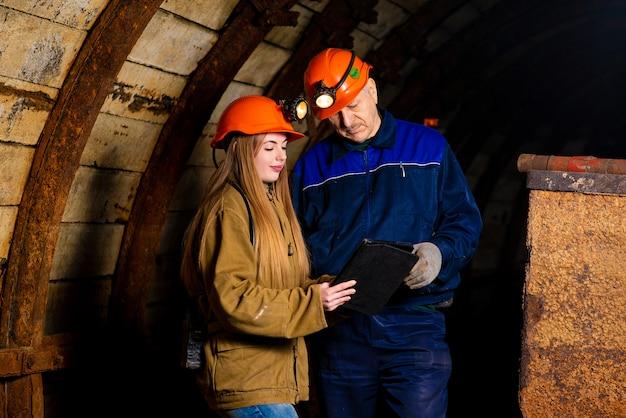 Uma linda garota e um homem idoso em um traje de proteção e capacete estão em pé em uma mina com um tablet em suas mãos