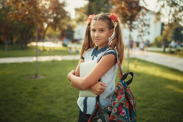 Uma linda garota em idade escolar está de pé ao lado de uma árvore e segurando um tablet. colegial, vestindo uma saia e uma camisa com sapatos