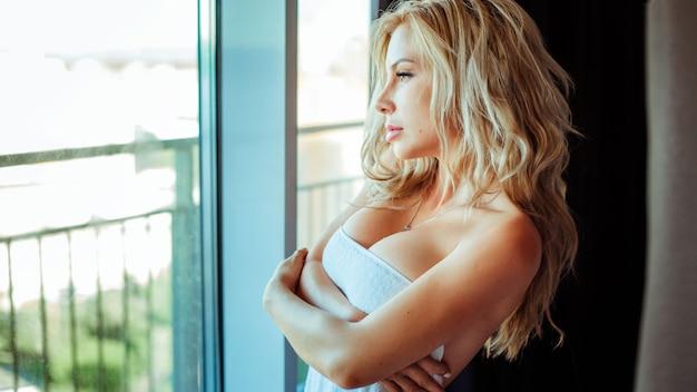 Uma linda garota em pé em uma toalha após o banho uma modelo atraente posa perto da janela semi-nua