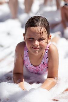 Uma linda garota em um maiô rosa encontra-se sob a espuma em uma festa de espuma na praia à beira-mar no verão ...
