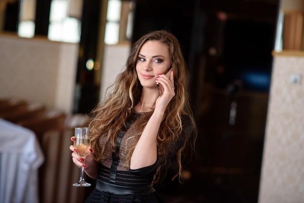 Uma linda garota em um restaurante se comunica por telefone.