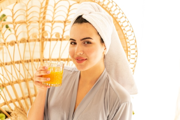 Uma linda garota em um roupão bebe suco de laranja. ela lindamente cumprimenta sua manhã cuidando de si mesma