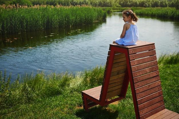 Uma linda garota em um vestido azul e dois rabos de cavalo se senta em cima de um banco de madeira e observa alegremente uma bela vista da perspectiva de saída do rio no campo