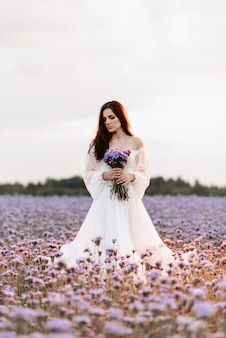 Uma linda garota em um vestido branco em um campo florido da provença em uma atmosfera romântica com um buquê nas mãos