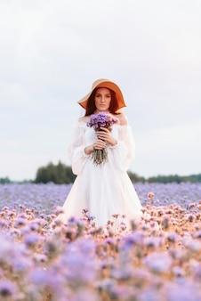 Uma linda garota em um vestido branco em um campo florido da provença em uma atmosfera romântica