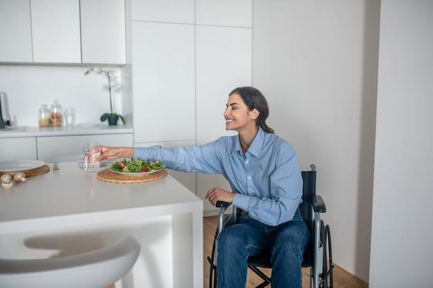 Uma linda garota em uma cadeira de rodas na cozinha de casa