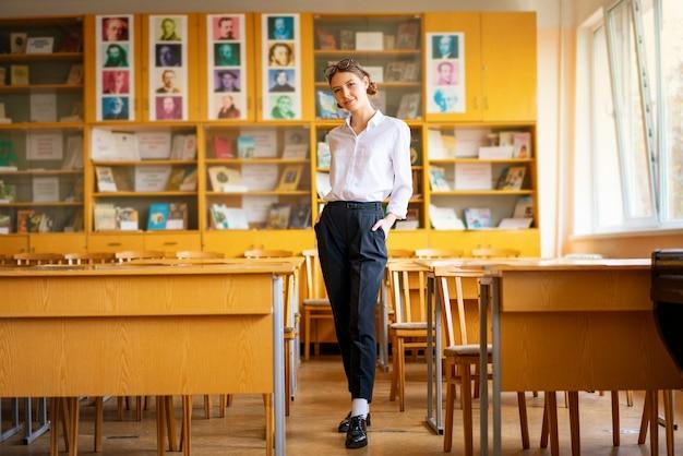 Uma linda garota em uma camisa branca fica na sala de aula entre as mesas
