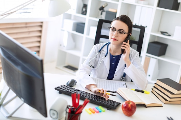 Uma linda garota em uma túnica branca está sentado à mesa, falando ao telefone e segurando a mão no teclado.