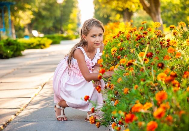 Uma linda garota encantadora em um lindo vestido rosa cheira malmequeres em um parque luminoso em um dia ensolarado de férias há muito aguardadas