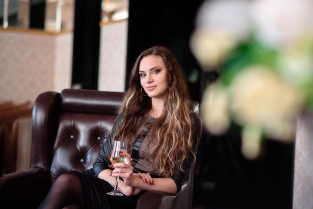 Uma linda garota está bebendo champanhe em um restaurante.