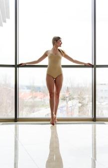 Uma linda garota está envolvida em coreografia perto de uma grande janela.