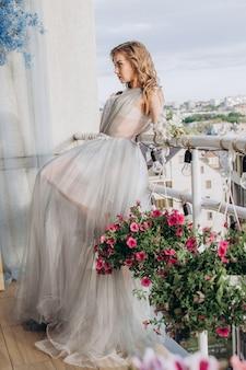 Uma linda garota está na varanda com um vestido longo e olha para longe