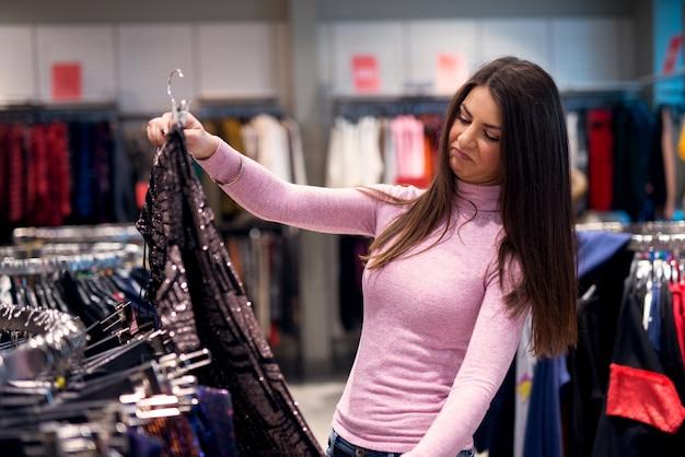 Uma linda garota está navegando na loja sem saber o que comprar.