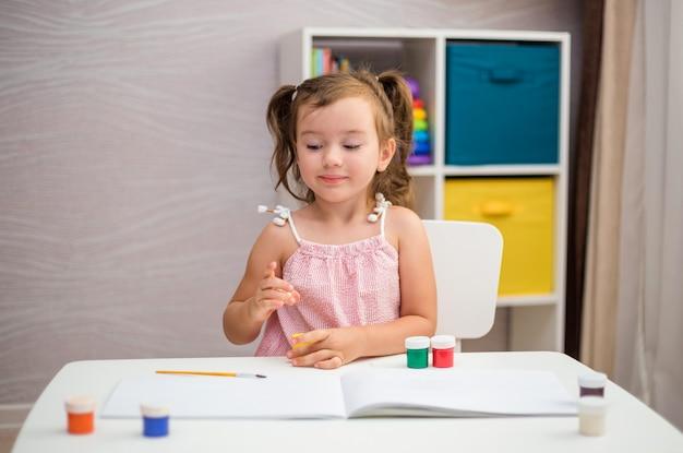 Uma linda garota está sentada em uma mesa e aprendendo a desenhar com um pincel