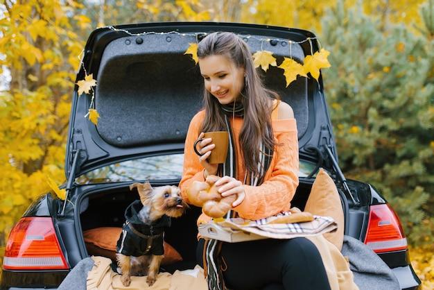 Uma linda garota está sentada no porta-malas de um carro preto com seu cachorro sorrindo, bebendo chá na hora do almoço, admirando a natureza da floresta e curtindo a liberdade