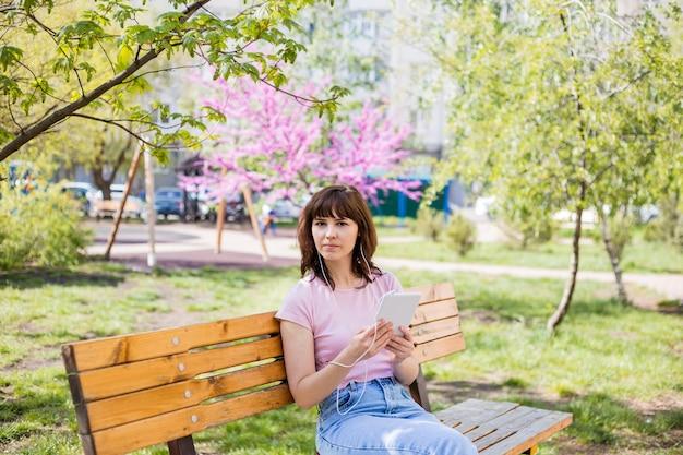 Uma linda garota está sentado em um banco com um tablet, fones de ouvido e parece longe. uma jovem garota em um top rosa e jeans está sentado em um banco na rua.