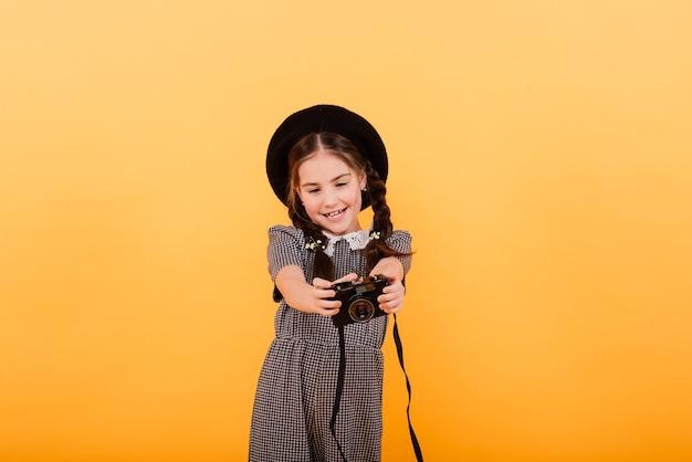 Uma linda garota fazendo foto sobre fundo amarelo.