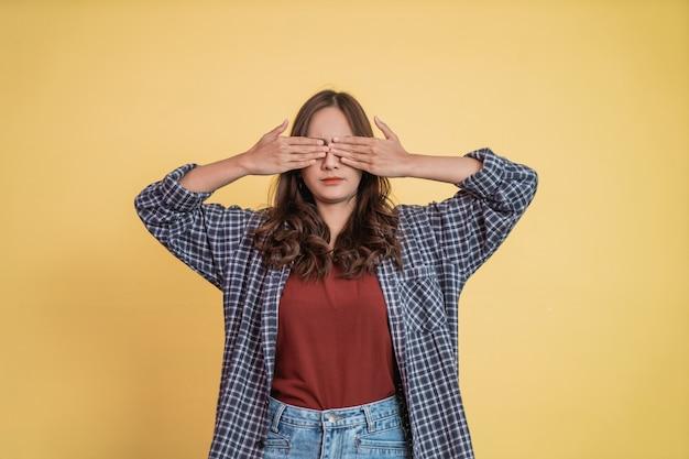 Uma linda garota fecha os olhos com as duas mãos