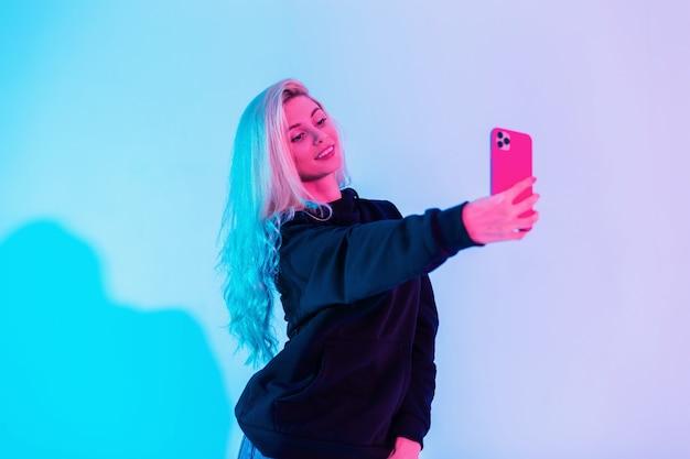 Uma linda garota feliz e glamourosa com um moletom preto faz uma foto de selfie no telefone no estúdio em um fundo de luz rosa e azul brilhante