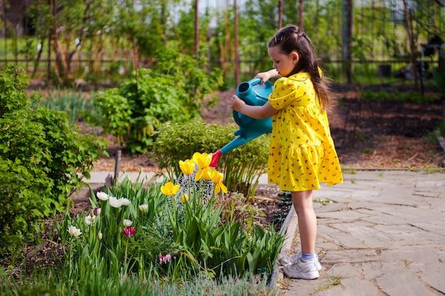 Uma linda garota feliz em um vestido amarelo está regando flores amarelas de um regador no jardim ...