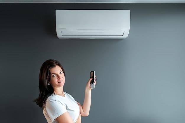 Uma linda garota fica sob ar condicionado e um fluxo de ar fresco contra uma parede cinza. o conceito de calor, ar fresco, refrigeração, frescura.