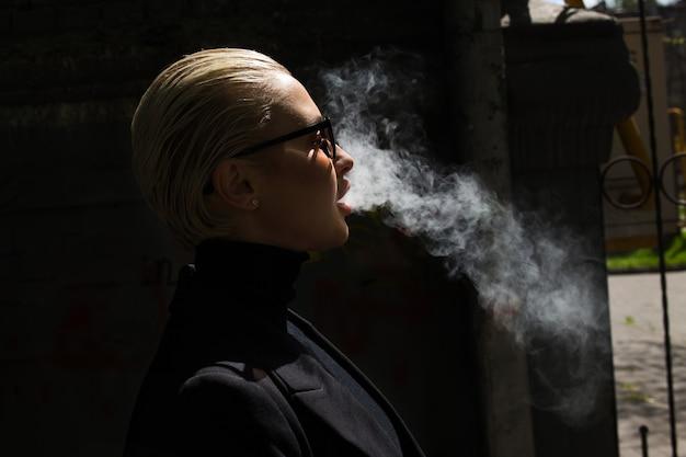 Uma linda garota fuma um vapor e solta a fumaça