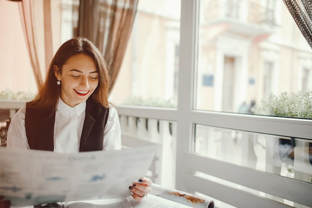 Uma linda garota lê uma revista em um café