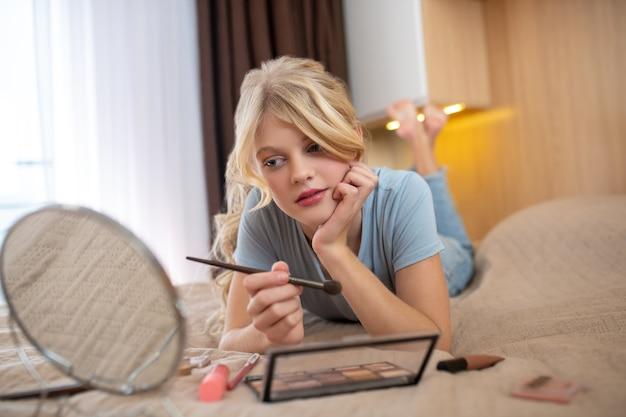 Uma linda garota loira adolescente deitada na cama com um espelho nas mãos