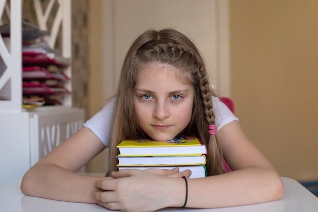Uma linda garota loira colocou a cabeça em uma pilha de livros coloridos que adora ler conceito de leitura de lazer