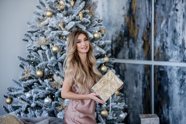 Uma linda garota loira elegante com cabelos cacheados em um vestido de pó de seda está segurando um presente perto da árvore de natal com bolas, uma guirlanda de luzes.