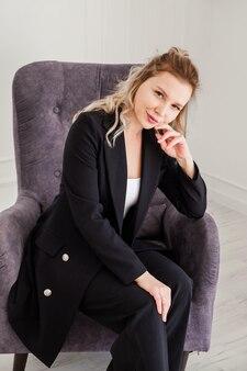 Uma linda garota loira em um terno preto se senta em uma cadeira e olha pensativamente para a câmera.