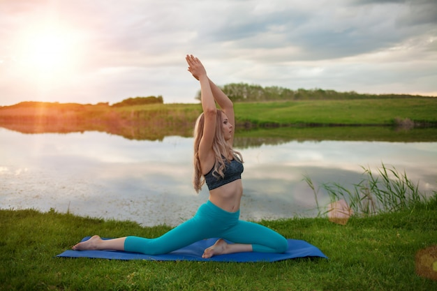 Uma linda garota loira está praticando ioga no lago ao pôr do sol. close-up suporta um estilo de vida saudável