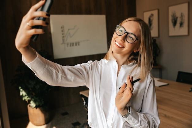 Uma linda garota loira feliz está transmitindo uma conversa ao vivo pelo telefone