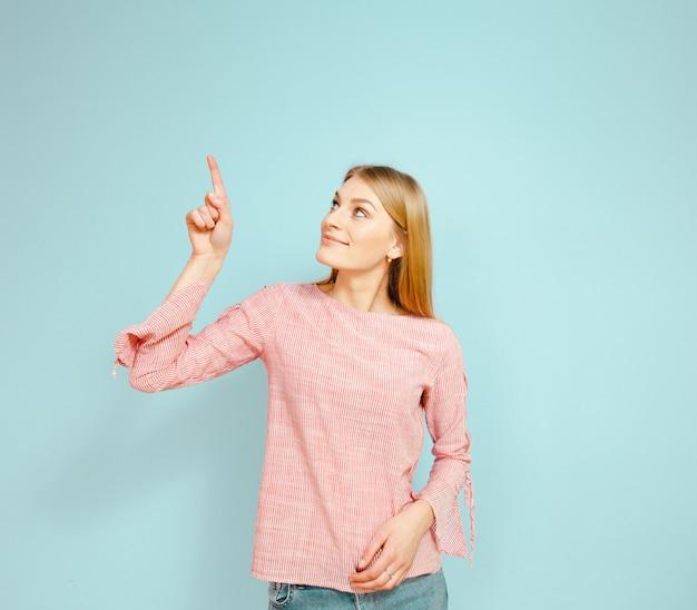 Uma linda garota loira mostrando gestos sobre um fundo azul.