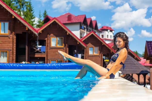 Uma linda garota magro relaxar na piscina em um dia quente de verão.