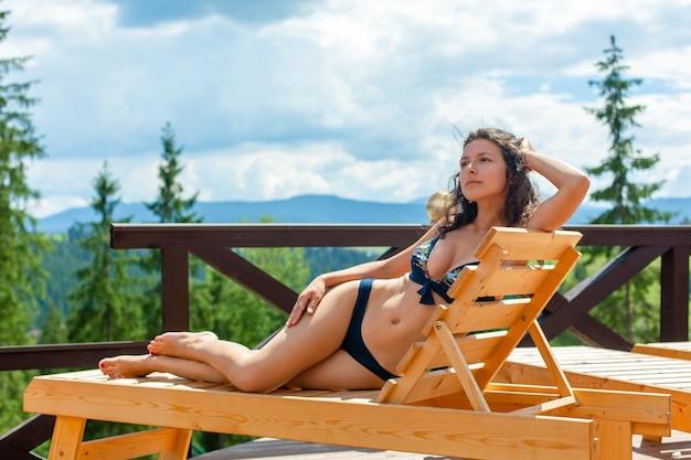 Uma linda garota magro se bronzeando e relaxando na espreguiçadeira em um dia quente de verão.