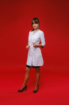 Uma linda garota médica segura um martelo reflexo e sorri para a câmera isolada em um fundo vermelho.