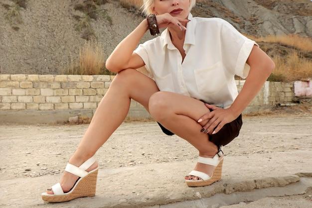 Uma linda garota na moda está localizada perto de uma colina na costa do mar no verão