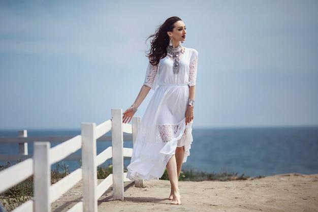 Uma linda garota, noiva, em um vestido branco, descalça, caminhando perto de uma cerca branca